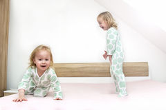 Two small identical twin sisters in identical pajamas, actively having fun on the parent& x27;s bed, Royalty Free Stock Photos