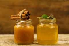 Two small jars honey with cinnamon and flowers on wooden background Stock Photos