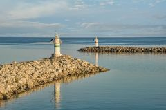 Two small jetty lighthouses at the entrance of a small harbor. With beautiful reflections royalty free stock images