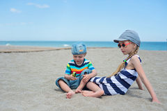 Two small kids sitting on the beach Stock Photography
