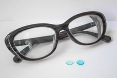 Optics for vision. Two small lenses for the eyes and thick female glasses. Myopia of a high degree. Modern correction of vision. Rigid contact lenses are blue Royalty Free Stock Image