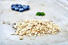 Two small piles of blueberries and raw oat flakes. Close up shot of two small piles of fresh blueberries and raw oat flakes with mint leaf between it. Dietary Stock Photo