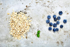 Two small piles of blueberries and raw oat flakes. Top view shot of two small piles of fresh blueberries and raw oat flakes with mint leaf between it. Dietary Royalty Free Stock Image