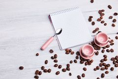 Two small pink cups on the table with a spoon, notepad and scattered coffee beans on a white wooden background. royalty free stock photography