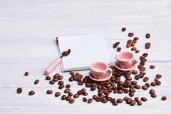 Two small pink cups on the table with a spoon, notepad and scattered coffee beans on a white wooden background. royalty free stock image