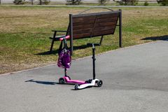 Two small pink and white children`s scooters are standing nearby in the park near the bench and the green lawn in anticipation of stock photography