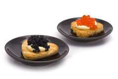 Two Small Plates with Heart-shaped Toasts with Caviar. Isolated on white Royalty Free Stock Photography