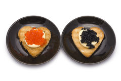 Two Small Plates with Heart-shaped Toasts with Caviar. Isolated on white Royalty Free Stock Photo