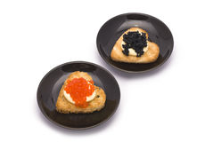 Two Small Plates with Heart-shaped Toasts with Caviar. Isolated on white Royalty Free Stock Photos