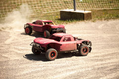 Two small radio controlled model cars racing in the dust Royalty Free Stock Photography