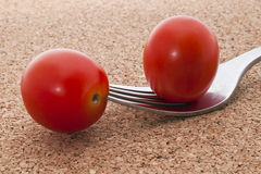Two small red tomatoes on fork Royalty Free Stock Images
