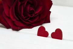 Two red wooden hearts and a red rose on a white wooden background. Valentine`s day or Love concept. stock images