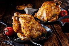 Two small roasted poussin or spring chickens stock image