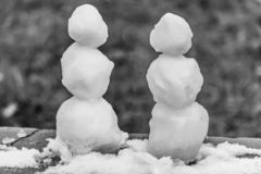 Two small rough snowmen with snow is on the black and white photo stock image