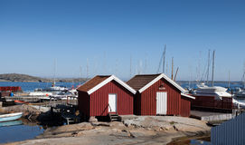 Two small sheds by the harbor. There are a lot of boats tied up in the background Stock Photography