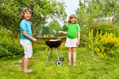 Two small sisters standing near BBQ and grilling Stock Images