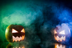Two small smoking pumpkins for Halloween with copy space. On black background Royalty Free Stock Image