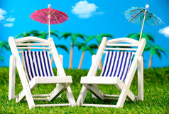 Two small sun loungers on grass Stock Photo