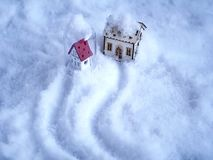 Two small toy houses with lighted illumination on the snow, paths on the snow. Concept of congratulations on Valentine, Christmas, family, love in the house stock photos