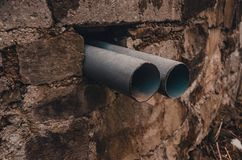 Two tubes in a hole of the wall stock photo