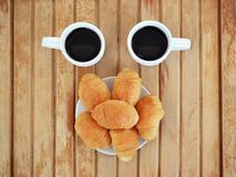 Two small white cups of coffee and some croissants on white saucer are on wooden table. Two small white cups of coffee and some croissants on white saucer are on royalty free stock photos