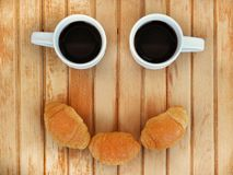 Two small white cups of coffee and three croissants look like smiling face. They are on light background of a warm shade, top view royalty free stock photo