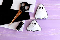 Two small white ghosts crafts, felt sheets, scissors, thread, needle on lilac wooden background. Hand Halloween decor idea Stock Image