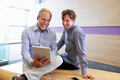 Two smart casually dressed men with tablet looking to camera Royalty Free Stock Photography
