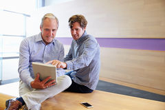 Two smart casually dressed men using a tablet computer Royalty Free Stock Photo