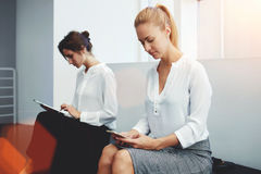 Two smart female reading information on touch pad and mobile phone during break between meeting with clients, Stock Photography