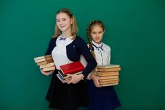 Two smart girls with books stand at Green School Board stock photography