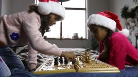 Two smart girls moving chess pieces on chessboard stock footage