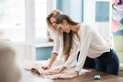 Two smart-looking pretty women wearing white shirts are leaning over the sewing table. Fashion, tailor`s workshop. stock image