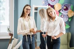 Two smart-looking pretty women wearing white shirts are standing in front of the mirror with tape-lines on their necks stock photo