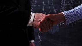Two smart people make handshake. Two smart scientists, male and female, make handshake closeup with mathematical equations on chalkboard. Super slow motion stock video