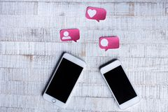 Two Smart Phone with Paper Cut Social Media Icons in Speech Bubble. Two White Smart Phone with Paper Cut Social Media Icons in Speech Bubble on Wood Table royalty free stock images