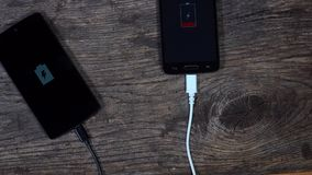 Two smart phones charging connected with cords. battery charge status. Two smart phones charging connected with cords. Screen showing battery charge status stock footage