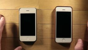Two smart phones expectation. Two smartphones waiting cal overhead shot stock video