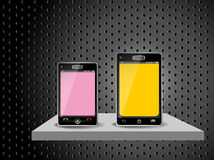 Two smart phones on a shelf Royalty Free Stock Photo