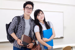 Two smart students standing in the class Stock Photos