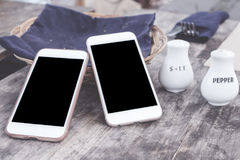Two smartphone in cafe on the wooden table. Smartphone with empty space black screen. royalty free stock images