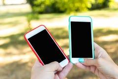 Two smartphones, blank screen