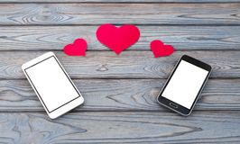Two smartphones with figures of hearts stock photo