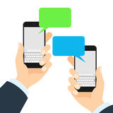 Two smartphones messaging. Two people holding mobile phones and chatting. Blue and green speech bubbles Stock Images