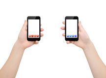 Two smartphones in two hands. Two hands holding two smartphones with red and blue bright applications icons, isolated on white, clipping path Royalty Free Stock Image
