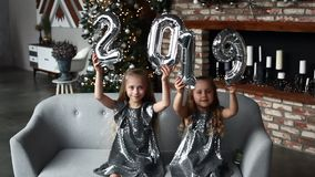 Two smile little girls Holding Hands New Year`s Balloons,. Number 2019. Christmas time. New year concept