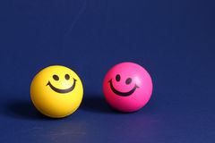 Two smiley faces. Yellow and pink smiley face on a blue background Royalty Free Stock Image