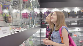 Two smiley girls choosing commodity in the shop of accessories. Two smiley girls choosing commodity on the shelf in the shop of accessories close up stock video footage