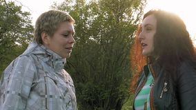 Two smiley girls friends talking in a green park. Two smiley merry and cheerful young women or girls friends walking in the green park outdoors in spring against stock video footage