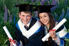 Two smiley Graduate outdoors stock images